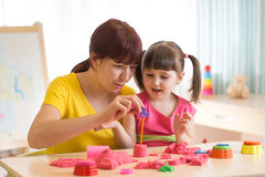 Cute little girl and mother playing with kinetic sand at home Stock Photo