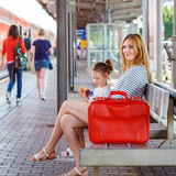 Cute little girl and mother on a railway station. Royalty Free Stock Image