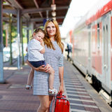 Cute little girl and mother on a railway station. Young women and her little daughter on a railway station. Kid girl and mother waiting for train and happy Stock Photography