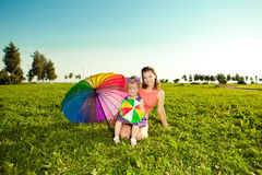 Cute little girl with mother  rainbow umbrella holding  in the p Royalty Free Stock Photo