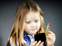 Cute little girl with mother's cosmetics, close-up portrait Stock Photo