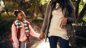 Cute little girl with mother walking outdoors. Cute little happy girl holding hand of a women and walking outdoors. Mother and daughter strolling outdoors and royalty free stock photography