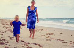 Cute little girl with mother walking on summer beach Royalty Free Stock Photos