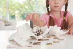 Cute little girl near broken piggy bank. Indoors Stock Image