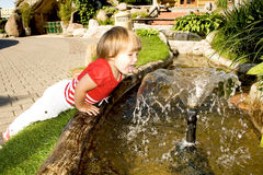 Cute little girl near a fountain. Little and active girl tries to drink from a water fountain Stock Images