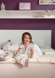 Cute little girl in nightdress on the bed in the morning. royalty free stock photography