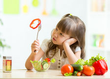 Cute little girl not wanting to eat healthy food. Cute kid girl not wanting to eat healthy food at kitchen royalty free stock images
