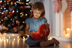 Cute little girl opening gift box in room decorated  for Christmas Royalty Free Stock Photography
