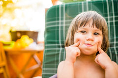 Cute little girl outside in garden holding her cheeks Royalty Free Stock Photography