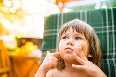 Cute little girl outside in garden holding her cheeks Royalty Free Stock Photo