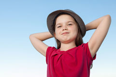 Cute little girl outside wearing a red shirt and a hat Stock Photos