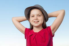 Cute little girl outside wearing a red shirt and a hat Stock Images