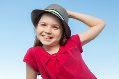 Cute little girl outside wearing a red shirt and a hat Royalty Free Stock Photos