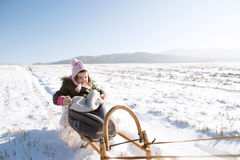 Cute little girl outside in winter nature, sitting on sledge Royalty Free Stock Images