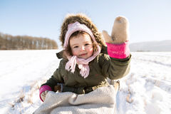 Cute little girl outside in winter nature, sitting on sledge. Cute little girl outside in winter nature on sunny day, sitting on sledge, waving Royalty Free Stock Photo