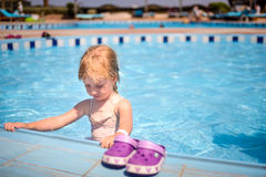 Cute little girl paddling in the kiddies pool. Cute little girl paddling kiddies pool resort standing in the water holding the edge tiles with her pink shoes Stock Photo