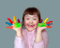 Cute little girl with painted hands. Isolated on grey background Stock Photos