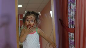 A cute little girl painted her face with paints.