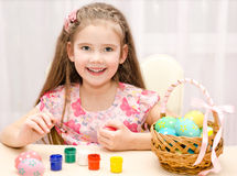 Cute little girl painting colorful easter eggs Royalty Free Stock Images