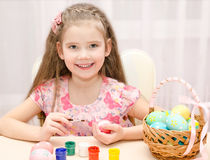 Cute little girl painting colorful easter eggs Stock Images