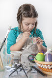 Cute little girl painting easter eggs Stock Photos