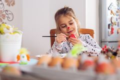 Cute little girl painting egg for Easter royalty free stock photos