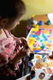 Cute little girl painting with paintbrush and colorful paints stock images