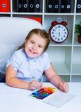 Cute little girl painting with watercolor stock photography