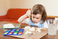 Cute little girl paints the dough figurines Stock Images