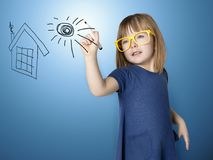 Cute little girl paints on glass houseand sun Royalty Free Stock Photo