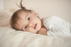 Cute little girl in pajamas on the bed in the morning Royalty Free Stock Images