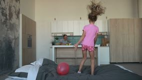 Cute little girl in pajamas jumping on bed stock video
