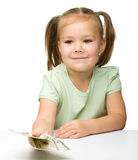Cute little girl with paper money - dollars Royalty Free Stock Images
