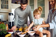 Cute little girl with parents preparing breakfast stock photo