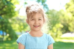Cute little girl in park. On sunny day Stock Photos