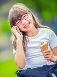 Cute little girl in the park on a sunny day with ice cream and mobile phone Stock Photos