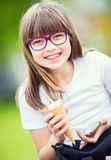 Cute little girl in the park on a sunny day with ice cream and mobile phone Royalty Free Stock Image