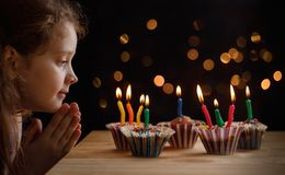 Cute little girl with party hat looking an the candles stock photography