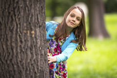 Cute little girl peeking from behind a tree. Fun. Stock Image