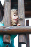 Cute little girl peeking out. Through wooden bars Royalty Free Stock Photo