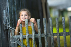 Cute little girl peeking out from behind the fence in the village. Happy. Stock Photography