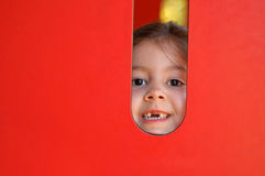 Cute little girl peeking in playground. Horizontal portrait of a cute preschooler girl smiling and peeking through the hole surrounded by red wall Royalty Free Stock Image