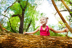 Cute little girl peeping behind fallen tree. Portrait of cute little girl peeping behind fallen tree in summer park stock photography