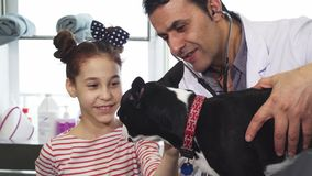 Cute little girl petting her dog during medical examination at the vet clinig. Adorable cheerful little girl petting her dog while professional mature male vet royalty free stock image