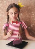 Cute little girl with photoprops is blowing out candle