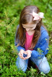 Cute little girl picking blueberries in the woods Royalty Free Stock Photos
