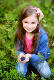 Cute little girl picking blueberries in the woods Stock Photography