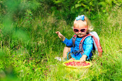 Cute little girl picking cranberries in summer forest Stock Photos