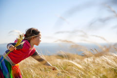 Cute little girl picking grasses. Cute little girl picking and gathering brown grasses on a meadow with the wind blowing through her long hair and sea in the stock photos