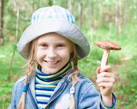 Cute little girl picking mushrooms in the forest Royalty Free Stock Photos